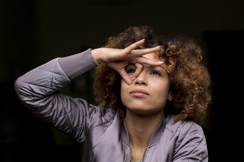 Portrait of woman building whole with her fingers looking through - HHLMF00010