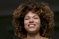 Portrait of happy woman with eyes closed in front of black background - HHLMF00013