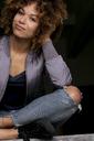 Portrait of smiling woman sitting against black background - HHLMF00019