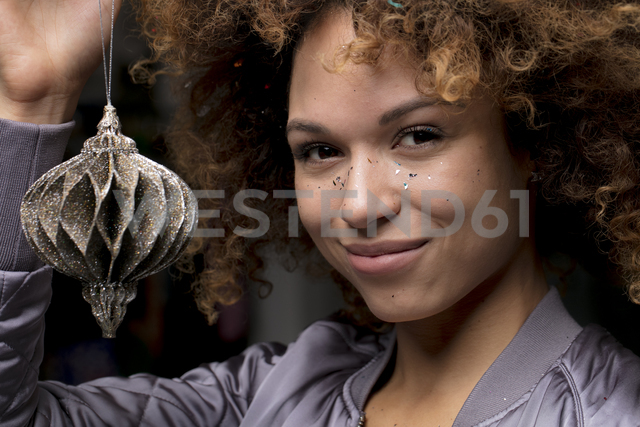 Portrait of smiling woman with Christmas bauble - HHLMF00028