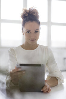 Portrait of smiling young woman  using tablet at table - HHLMF00037