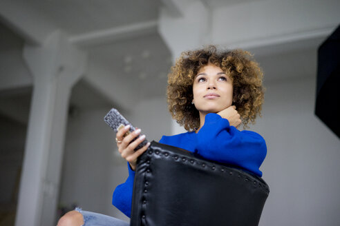 Portrait of woman with cell phone sitting on armchair - HHLMF00049