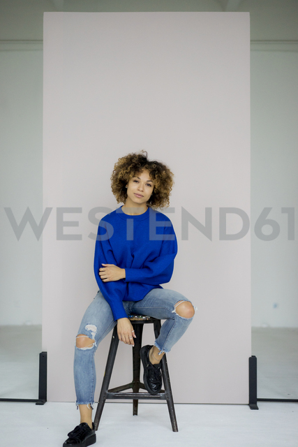 Portrait of serious woman wearing blue pullover sitting on stool - HHLMF00055