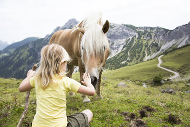 Austria, South Tyrol, young girl with horse on meadow - FKF02866