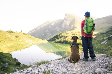 Austria, South Tyrol, young boy standing next to his dog - FKF02881