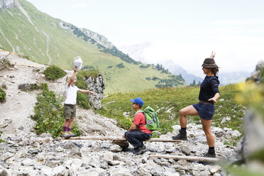 Austria, South Tyrol, family balancing on wood - FKF02884