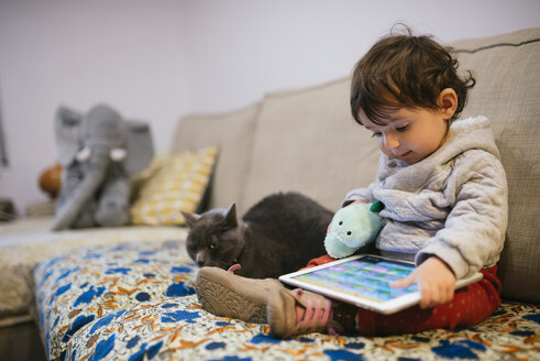 Baby girl sitting on couch watching videos on a tablet with a cat - GEMF01834