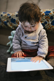 Baby girl watching videos on a tablet at home - GEMF01837