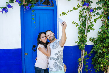 Morocco, Tanger, couple taking selfie with smartphone in front of blue door - KIJF01796