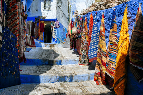 Morocco, Chefchaouen, carpet shop presenting offers outside - KIJF01811