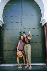 Morocco, Chefchaouen, two women taking selfie with smartphone in front of green portal - KIJF01814