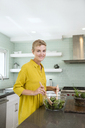 Portrait of smiling young woman preparing salad in kitchen - MFRF01066