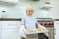 Smiling boy holding baking tray with cinammon buns - MFRF01078