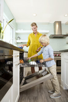 Boy helping mother clearing the dishwasher in kitchen - MFRF01081