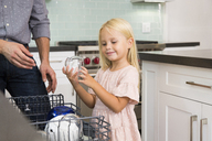 Girl helping father clearing the dishwasher in kitchen - MFRF01084