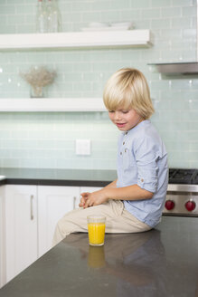 Boy in kitchen with glass of orange juice - MFRF01087