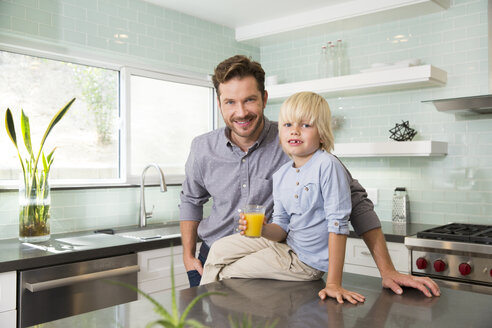 Portrait of boy with father in kitchen holding glass of orange juice - MFRF01090