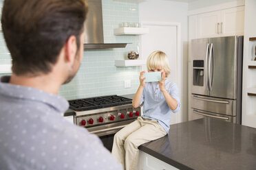 Son taking cell phone picture of father in kitchen - MFRF01093