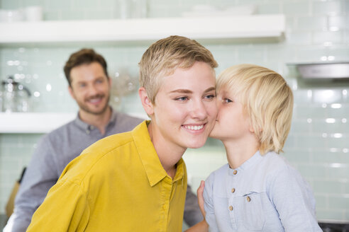 Son kissing mother in kitchen with father in background - MFRF01096