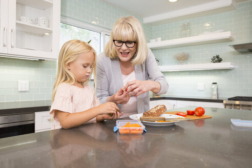 Grandmother and granddaughter preparing lunch box in kitchen together - MFRF01099