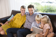 Family sitting on couch at home using tablet - MFRF01105