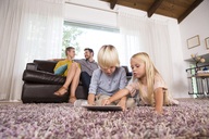 Brother and sister using tablet on carpet in living room with parents in background - MFRF01108