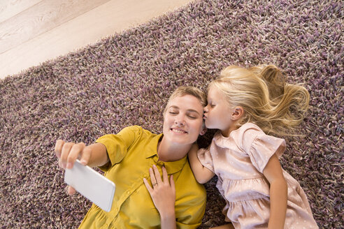 Smiling mother and daughter lying on carpet taking a selfie - MFRF01111