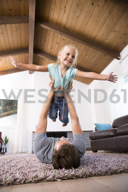 Father playing with daughter on carpet in living room at home - MFRF01114 - Michelle Fraikin/Westend61