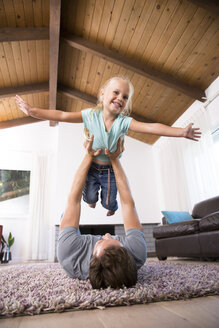 Father playing with daughter on carpet in living room at home - MFRF01114