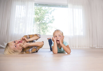 Brother and sister lying on the floor at home grimacing - MFRF01117