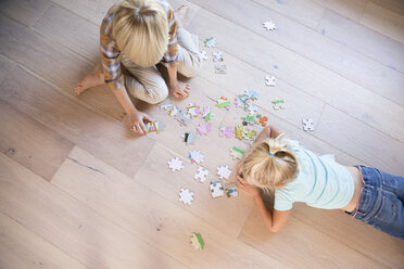 Brother and sister lying on the floor at home playing jigsaw puzzle - MFRF01120
