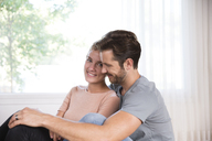 Smiling couple relaxing at home in front of window - MFRF01123
