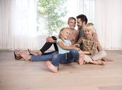 Relaxed family sitting on the floor at home - MFRF01126