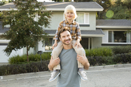 Portrait of boy on father's shoulders in front of their home - MFRF01129