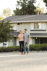 Smiling couple standing in front of their home - MFRF01132