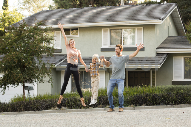 Happy family with son jumping in front of their home - MFRF01135 - Michelle Fraikin/Westend61