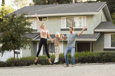 Happy family with son jumping in front of their home - MFRF01135