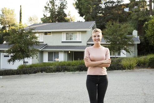 Portrait of smiling woman in front of her home - MFRF01141