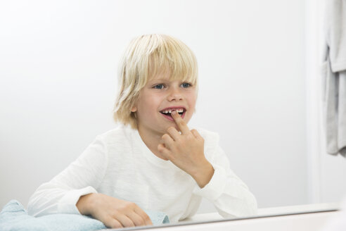 Smiling boy looking in bathroom mirror examining his teeth gap - MFRF01150
