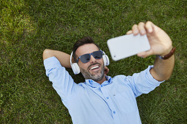 Portrait of laughing man lying on a meadow taking selfie with smartphone, top view - BSZF00139