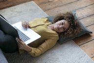 Smiling young woman lying on the floor at home with laptop - HHLMF00062