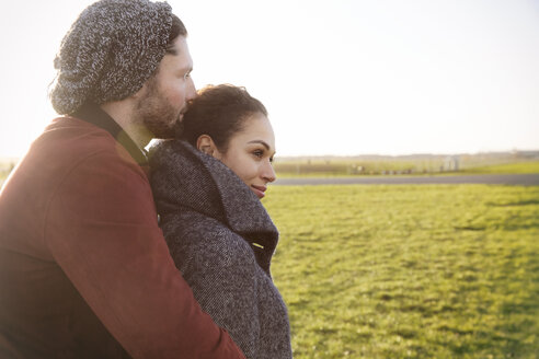 Affectionate young couple embracing on a meadow - HHLMF00077