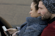 Young couple with cell phone close together outdoors - HHLMF00083