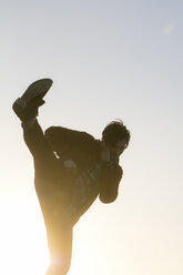 Young man doing a kickboxing move outdoors at sunset - HHLMF00089