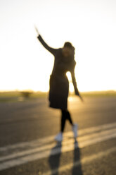 Blurred view of woman walking on a lane at sunset - HHLMF00101