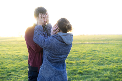 Young couple standing on a meadow covering their eyes - HHLMF00104