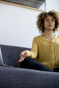 Young woman sitting on couch at home next to laptop meditating - HHLMF00113