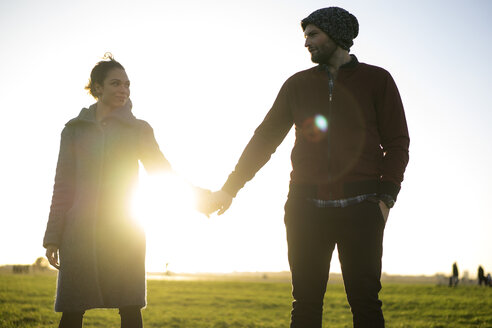 Affectionate young couple standing hand in hand on a meadow at sunset - HHLMF00143