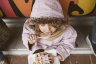 Belgium, little girl eating Belgian waffle in winter outdoors - KMKF00107