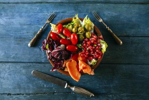 Papaya salad, pomegranate, lettuce, tomato, olives and endive on blue wood - KIJF01819
